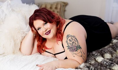 red haired curvy women lay on a bed
