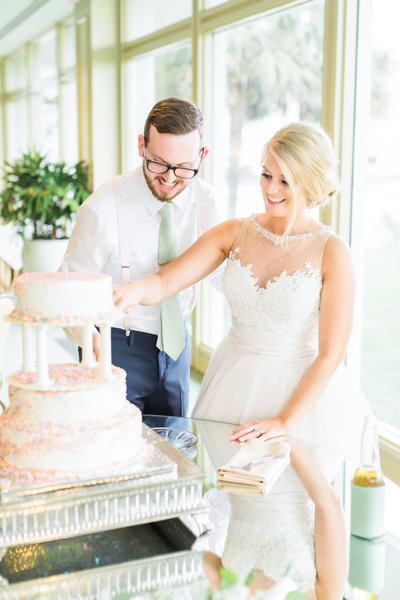 bride and groom cutting cake at reception