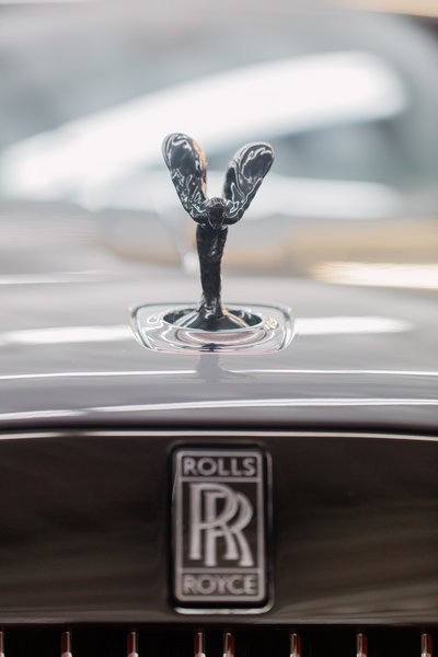 Closeup of Rolls Royce hood ornament inside car storage facility