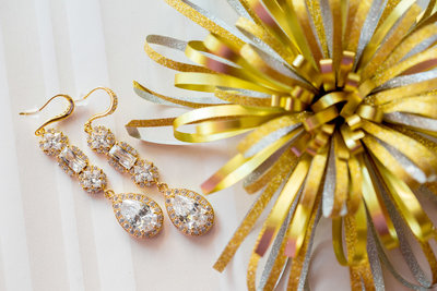 Gold earrings and bow flat lay