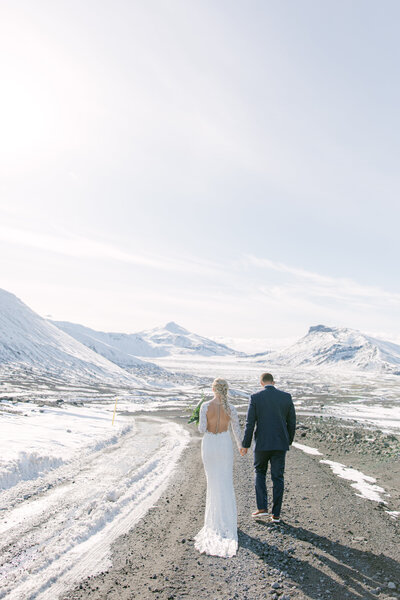 bride and groom in Iceland walking away from the camera with icy mountains in front of them