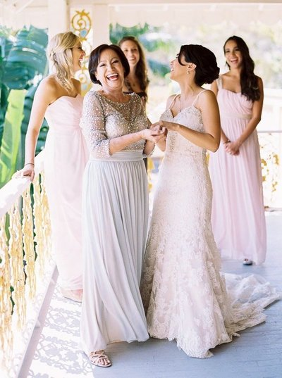 bride and mother laughing with bridesmaids