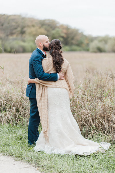 couple hugging in rustic wheat field