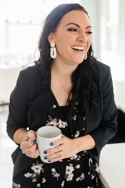 Dolly of Dolly DeLong Photography is standing up and laughing while holding a cup of coffee in a white coffee mug for her branding photos