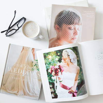 A mug and sample wedding pictures on the desk in branding and website design studio for photographers