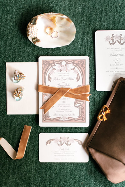 invitation suite styled with vintage earrings on a vibrant green carpet with velvet brown ribbon
