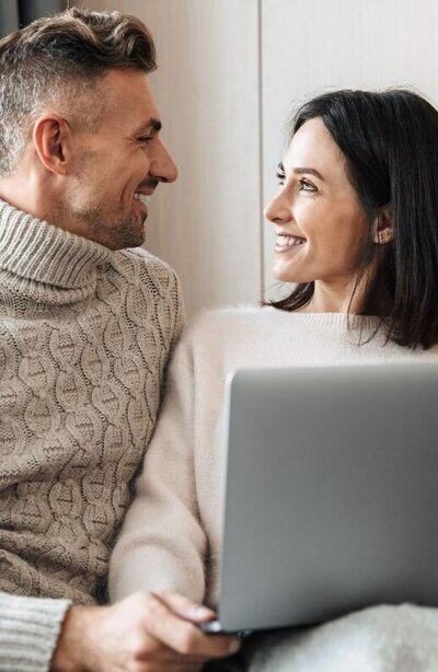 A couple smile at one another while holding a laptop. This could represent having an online therapy session from the comfort of their home. We offer online therapy in Florida, online couples counseling, online marriage counseling, and other services.