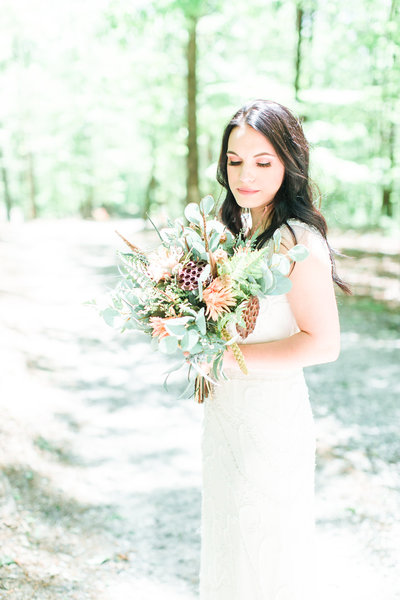 black hair bride holds large honeycomb bouquet in the forest