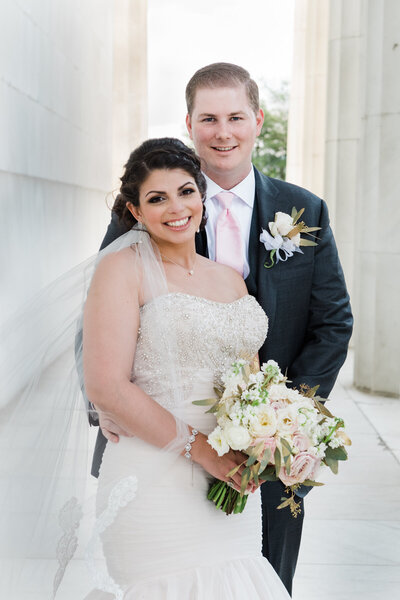 Photo of wedding couple standing in a walkway at the Lincoln Memorial surrounded by marble columns.The groom is standing behind the bride with her veil draped over her shoulder and arm while holding a beautiful bouquet of light colored roses.