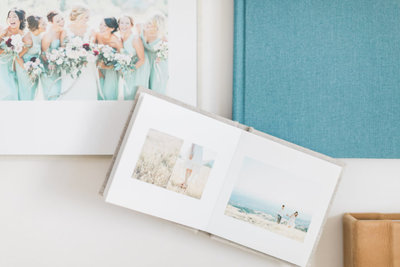 White background with linen photo album lying open and teal photo album placed underneath it