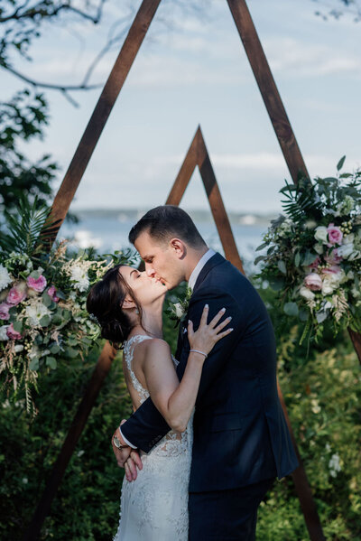 A couple share a kiss in front of asymetrical arches