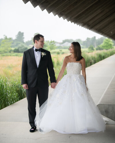 a bride and groom looking at each other on a covered path