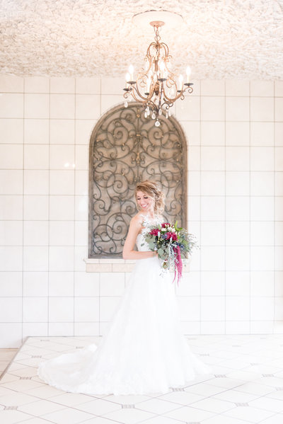 Bride looks over shoulder in white hallway