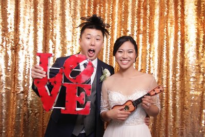 gold backdrop with bride and groom holding a love sign.