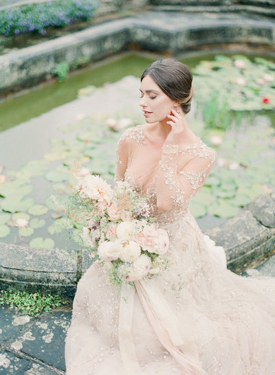 Bride in wedding dress posing by a pond while holding a a bouquet of flowers