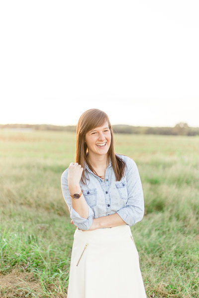 Lindsey Brown is the owner and photographer at Lindsey Brown Photography. She stands smiling in a field in this photo.