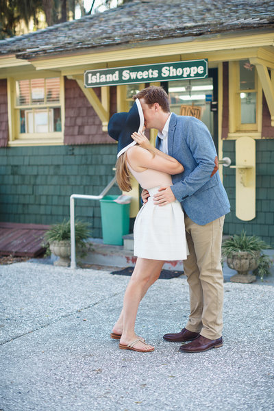 Bride Cups Floppy Hat around Face as Fiance Kisses her in Front of a Candy Shoppe at their Jekyll Island Engagement Photos
