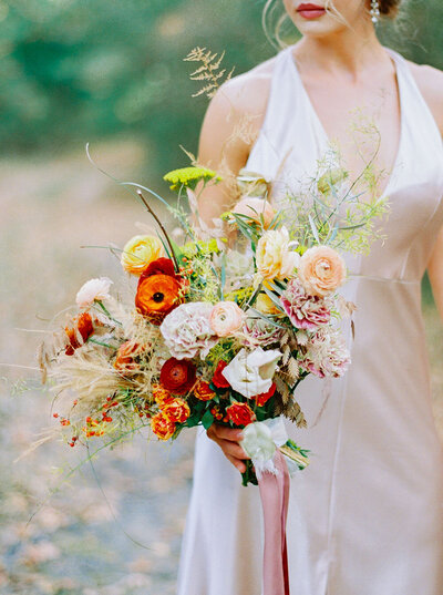 Textural autumn bridal bouquet with wispy grasses, plus vibrant red, peach and yellow flowers