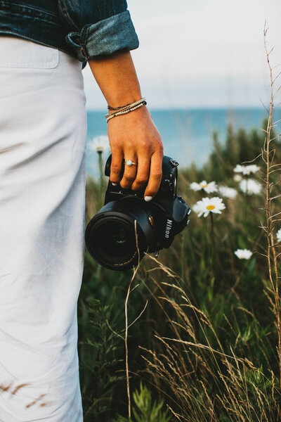 woman holding camera in a field