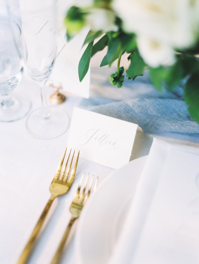 fine art wedding reception place setting with gold flatware and hand lettered place cards