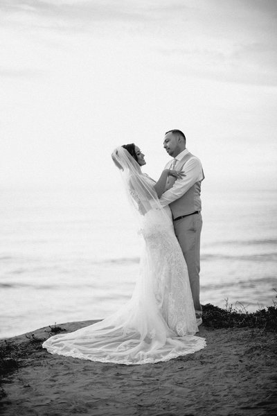 Black and white image of a couple hugging on the cliffs of Sunset Cliffs San Diego