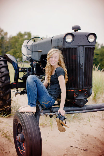 young woman posing on the wheel of a black tractor