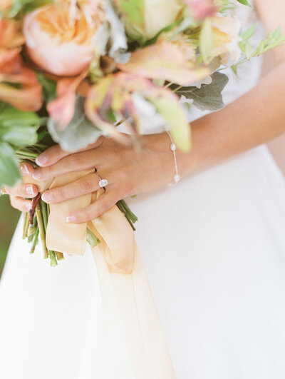 bride holding bouquet and showing off wedding ring