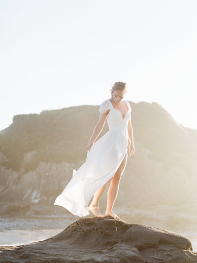 bride standing on rock at the beach in the wind
