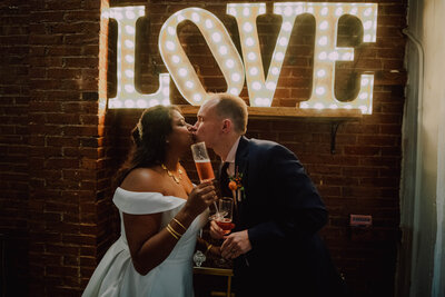 bride wearing white dress holding champagne glass kisses groom wearing blue tux in from of neon love sign in old city collective shot by philadelphia wedding photographer alex medvick