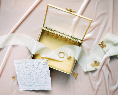 Fine art wedding photography details of gold ring box, colored yellow  wedding ring, and invitations.
