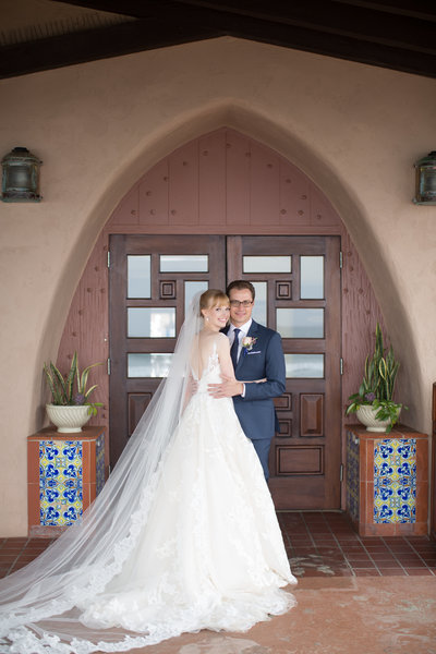 Bride and Groom in front of door at their wedding at The La Jolla Beach and Tennis club