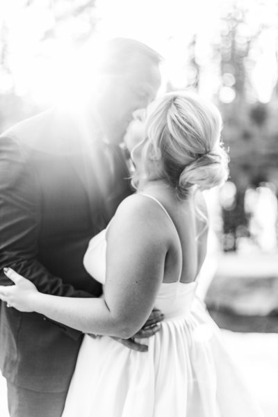 Bride and groom kissing black and white