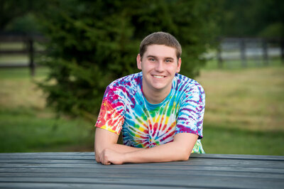 boy in tie dyed t-shirt on bed of truck