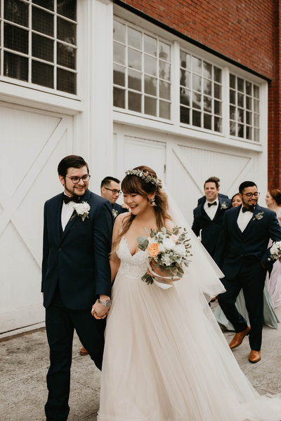 Bride & groom walk hand in hand on their wedding day with their wedding party in Portland, Oregon