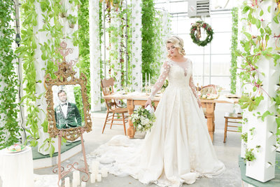 Bride in wedding gown stands in greenery decorated room