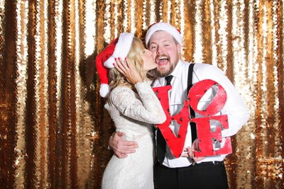 bride and groom having an amazing time front of a photo booth