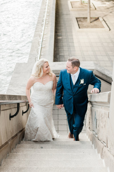 couple walking up staircase by river