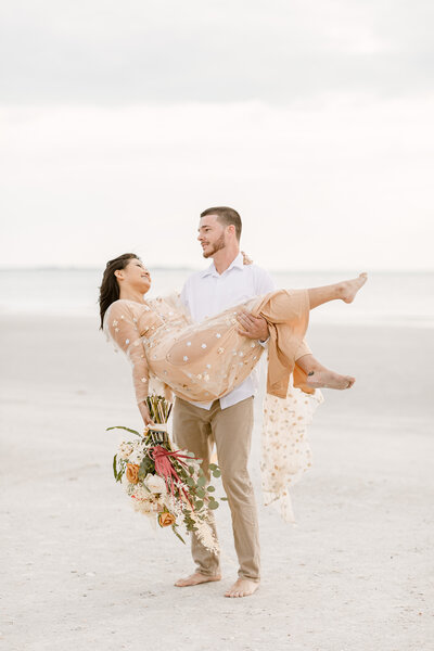 Groom embraces bride from behind who holds a large bouquet on the beach