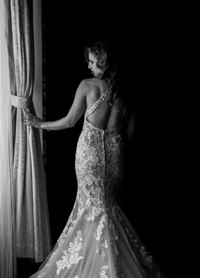 Black and white photo of a bride beside a window at Rosewood Hotel Georgia