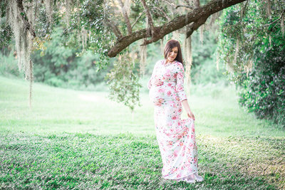 A mother-to-be looks down and holds her dress in Wauchula, Florida.