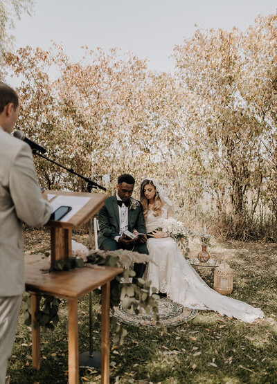 Bride and groom reading scripture during their wedding ceremony