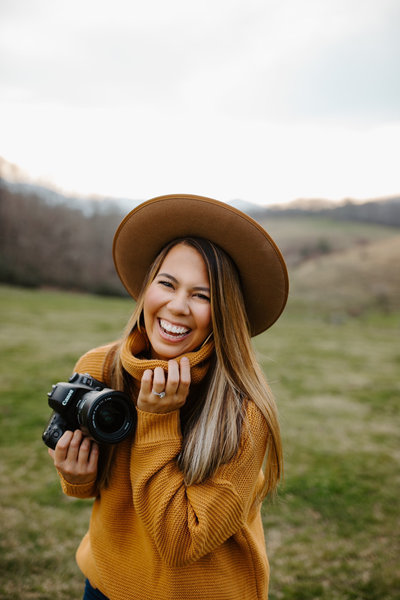 woman holding camera and smiling