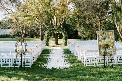 An outdoor wedding ceremony with flowers down the aisle and a large wedding arch