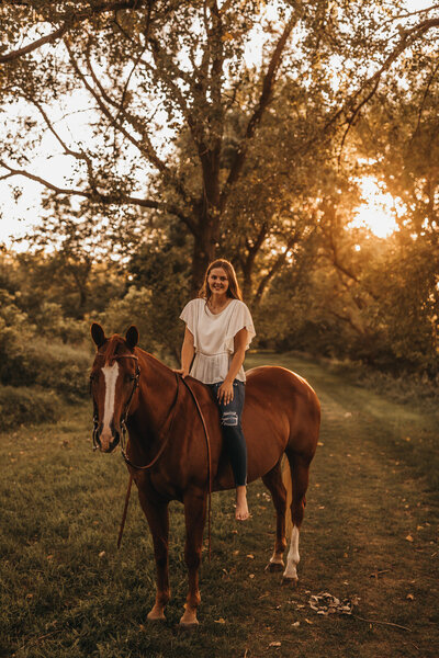 Senior on horse with sunsetting in the back