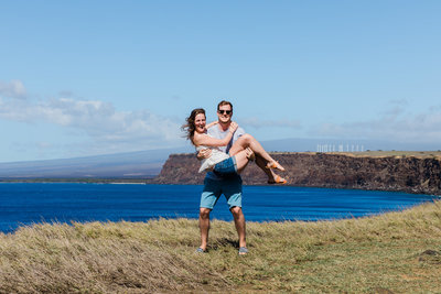 Man holding a woman on the edge of a cliff with the ocean in the background, in Hawaii