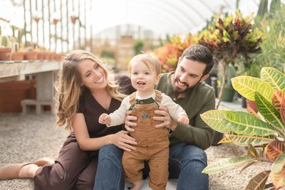 a family of three is taking their family portraits at the hewitt garden center in nashville Tennessee by Dolly DeLong Photography