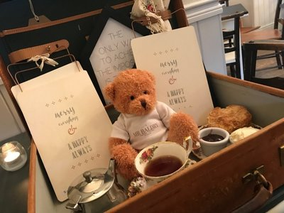 Photo of Mr Baldry (a teddy bear mascot) sat in a tray with tea, cakes and cards.