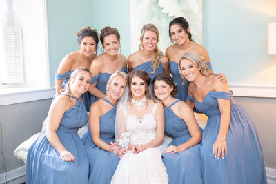 Bride smiles surrounded by her bridesmaids on wedding day