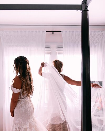 woman putting veil on bride