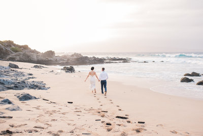 Couple runs to the ocean during sunset in Kapalua